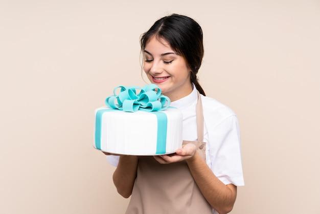 Chef pâtissier femme tenant un gros gâteau