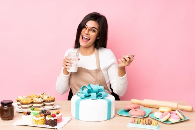 Chef pâtissier avec un gros gâteau dans une table