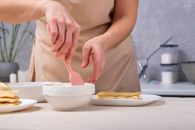 Le chef pâtissier prépare la crème pour le gâteau. processus de fabrication de tarte. mains avec vaisselle
