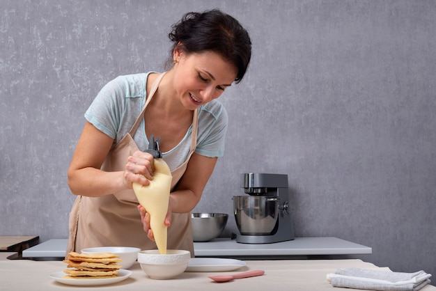 Le chef pâtissier prépare le gâteau à partir de sablés et de crème. processus de fabrication du gâteau.