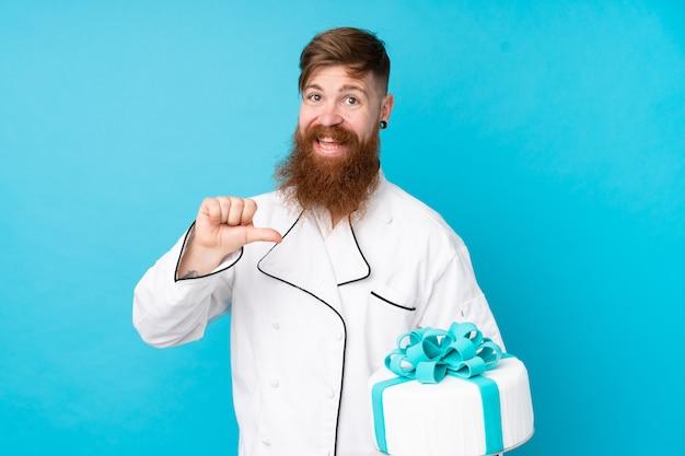 Chef pâtissier rousse avec longue barbe tenant un gros gâteau sur le mur bleu isolé fier et satisfait de lui-même