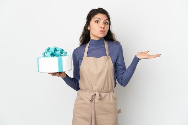 Chef pâtissier russe tenant un gros gâteau isolé sur fond blanc ayant des doutes tout en levant les mains