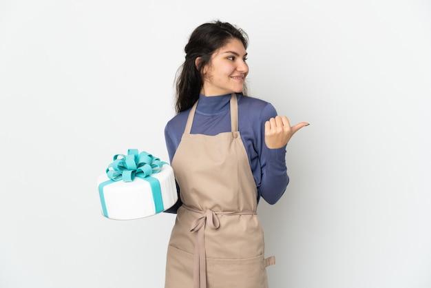 Chef pâtissier russe tenant un gros gâteau isolé sur fond blanc pointant vers le côté pour présenter un produit