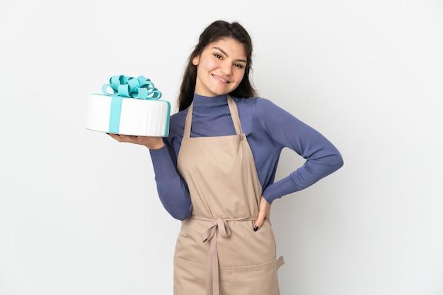 Chef pâtissier russe tenant un gros gâteau isolé sur fond blanc posant avec les bras à la hanche et souriant