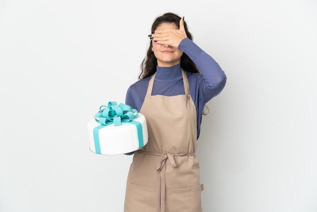 Chef pâtissier russe tenant un gros gâteau isolé sur un mur blanc couvrant les yeux par les mains. je ne veux pas voir quelque chose
