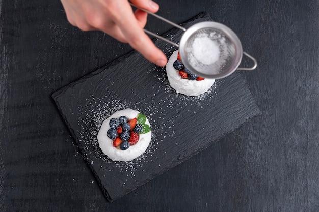 Le chef pâtissier saupoudre de sucre glace les gâteaux aux petits fruits. processus de fabrication de gâteaux, vue de dessus.