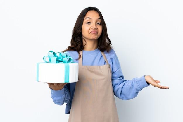 Chef pâtissier tenant un gros gâteau sur fond blanc isolé ayant des doutes tout en levant les mains