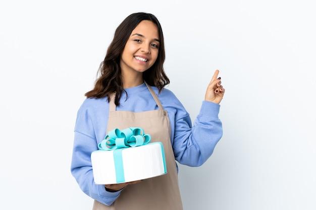 Chef pâtissier tenant un gros gâteau isolé sur fond blanc heureux et pointant vers le haut