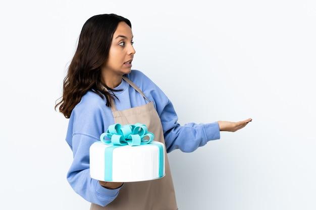 Chef pâtissier tenant un gros gâteau sur un mur blanc isolé avec une expression de surprise tout en regardant côté