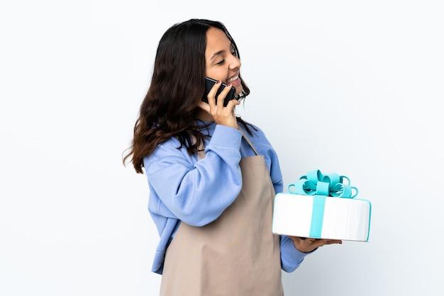 Chef pâtissier tenant un gros gâteau sur un mur blanc isolé en gardant une conversation avec le téléphone mobile avec quelqu'un