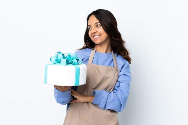 Chef pâtissier tenant un gros gâteau sur un mur blanc isolé heureux et souriant