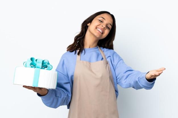 Chef pâtissier tenant un gros gâteau sur un mur blanc isolé présentant et invitant à venir avec la main