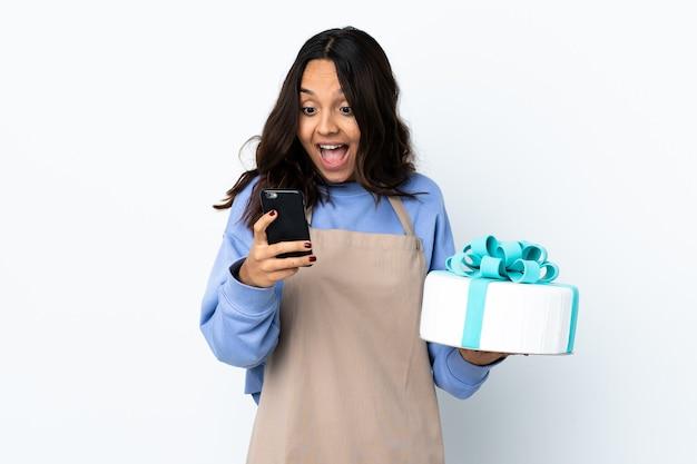 Chef pâtissier tenant un gros gâteau sur un mur blanc isolé surpris et envoyant un message