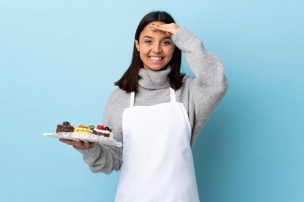 Chef pâtissier tenant un gros gâteau sur le mur bleu isolé saluant avec la main avec une expression heureuse