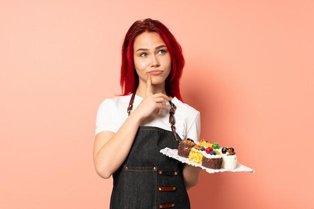 Chef pâtissier tenant un muffins isolé sur fond rose ayant des doutes tout en levant