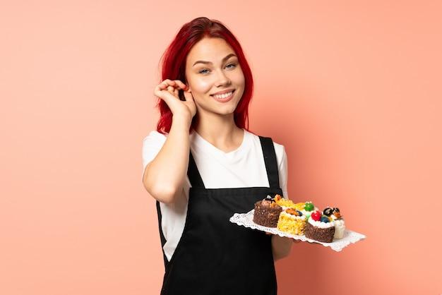 Chef pâtissier tenant un muffins isolé sur fond rose en riant