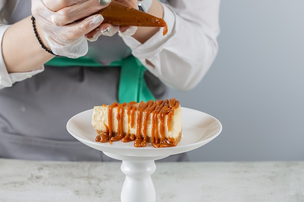 Le chef pâtissier verse du caramel sur une tranche du cheesecake le plus frais sur une plaque blanche