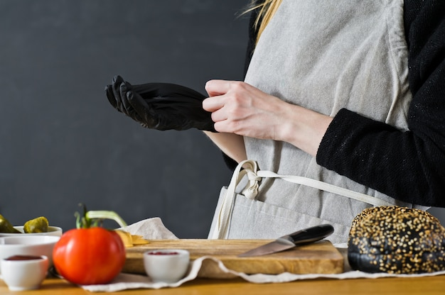Le chef porte des gants à la cerise. le concept de la cuisson d'un burger noir.