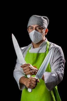 Chef posant sérieux avec ses couteaux sur fond noir en utilisant le protocole de sécurité anti-covid