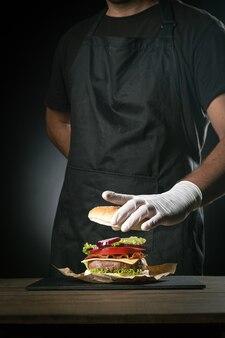 Chef préparant un hamburger sur fond noir.