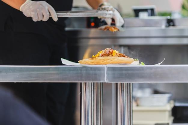 Chef préparant un sandwich sur un camion de cuisine en direct.