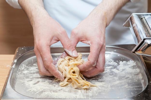 Le chef prépare avec amour des fettuccines italiennes traditionnelles. processus de fabrication de nouilles fraîches maison