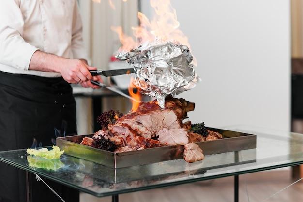 Chef prépare la dinde au four sur un plateau au feu. dinde rôtie.