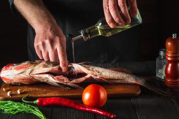 Le chef prépare du poisson frais carpe à grosse tête avec de l'huile d'ajout. préparation à la cuisson des aliments pour poissons. environnement de travail dans la cuisine du restaurant ou du café