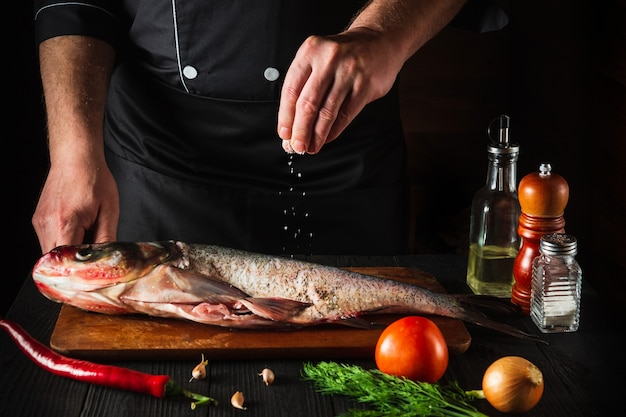 Le chef prépare du poisson frais carpe à grosse tête en saupoudrant de sel avec les ingrédients. préparation à la cuisson des aliments pour poissons. environnement de travail dans la cuisine du restaurant