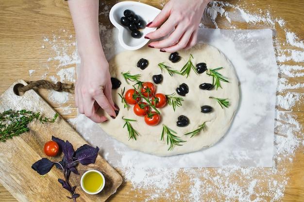 Le chef prépare focaccia, met les olives sur la pâte.