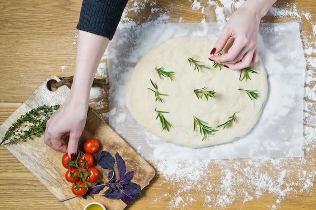 Le chef prépare focaccia, pose des tomates sur la pâte.