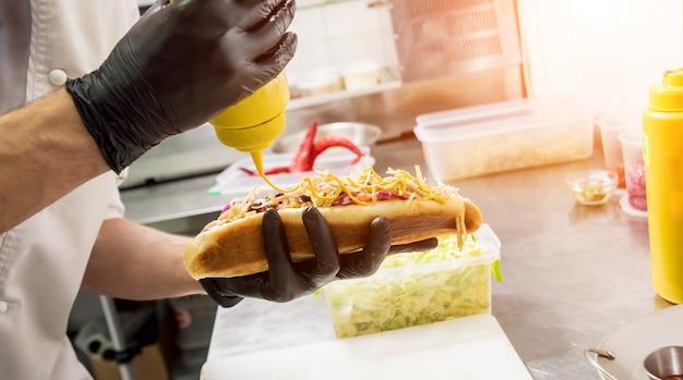 Le chef prépare un hot-dog sur un grill.