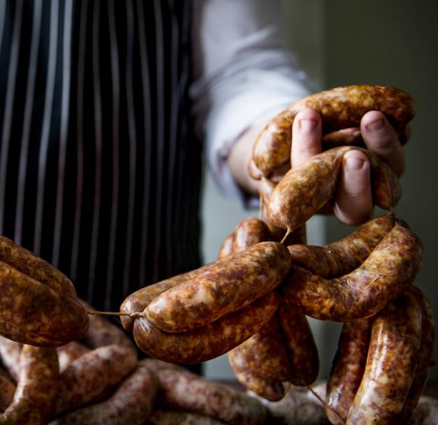 Un chef prépare une idée de recette de photographie de nourriture de saucisses