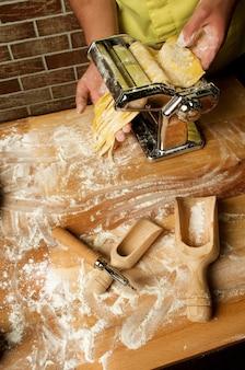 Le chef prépare la pâte pour les fettuccini et la soupe