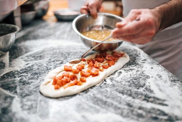Chef prépare une pizza macédonienne. fermer.