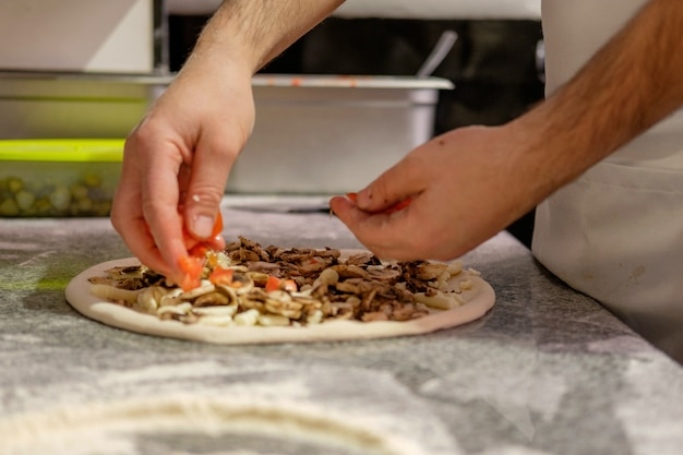 Le chef prépare la pizza