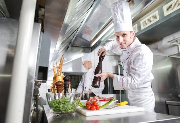 Le chef prépare un plat dans la cuisine du restoran.