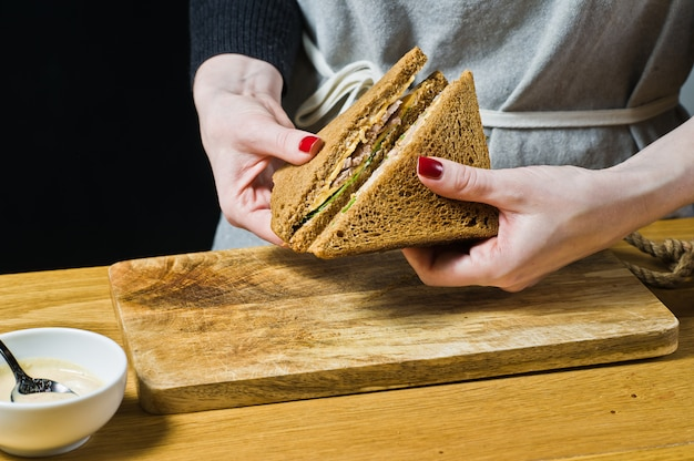 Le chef prépare un sandwich au pain noir.
