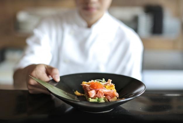 Chef présentant un tartare de poisson dans une assiette noire