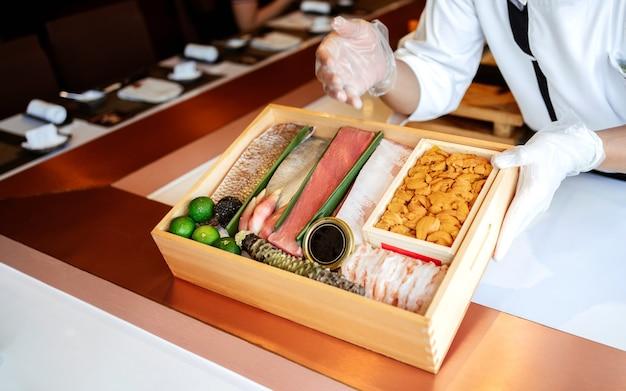Le chef présente les ingrédients frais de première qualité dans une boîte en bois avant de préparer le repas omakase