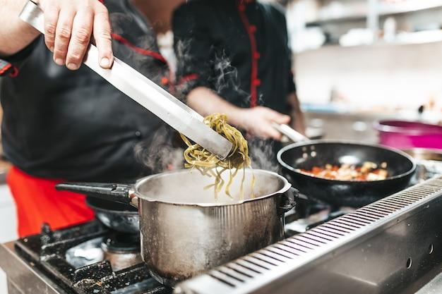 Chef professionnel en cuisine restaurant cuisine pâtes tagliatelles.