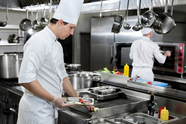 Chef professionnel dans la cuisine rôtit les légumes sur le gril
