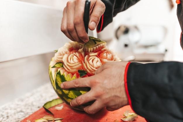 Chef professionnel dans un restaurant de cuisine découpant la pastèque.