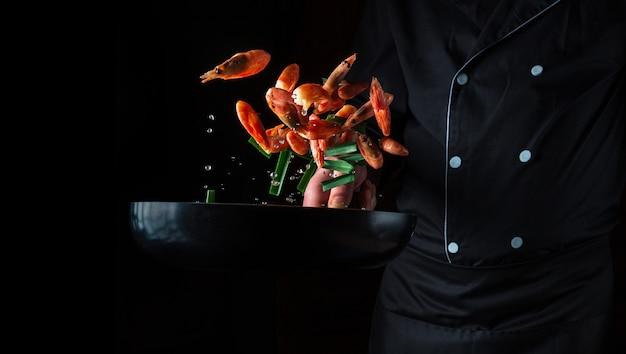 Le chef professionnel fait cuire des crevettes dans une casserole avec des légumes. cuisson des fruits de mer, de la nourriture végétarienne saine et de la nourriture sur fond noir. gel en mouvement. espace publicitaire gratuit