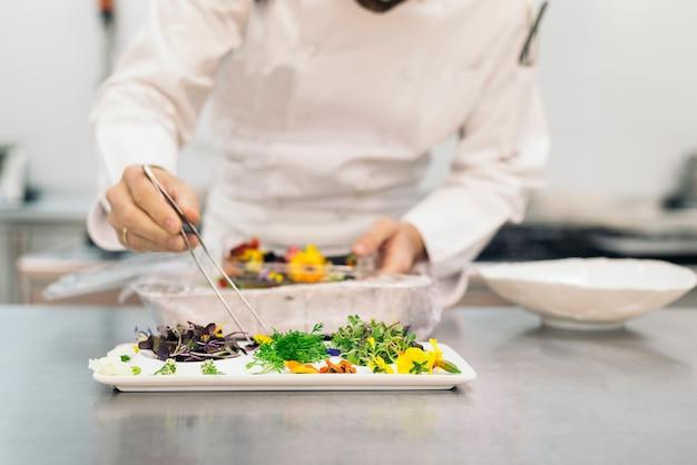 Chef professionnel masculin cuisinant dans une cuisine.
