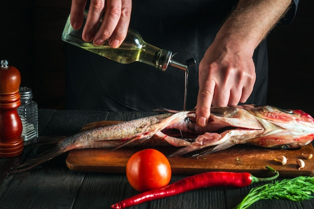 Un chef professionnel prépare des carpes à grosse tête de poisson frais avec de l'huile d'ajout préparation à la cuisson des aliments pour poissons