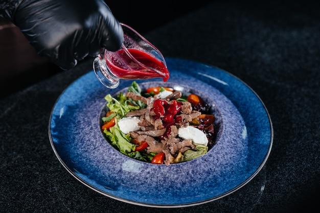 Un chef professionnel prépare une délicieuse salade fraîche de légumes verts et de veau juteux dans un restaurant moderne et élégant. cuisiner dans un restaurant.