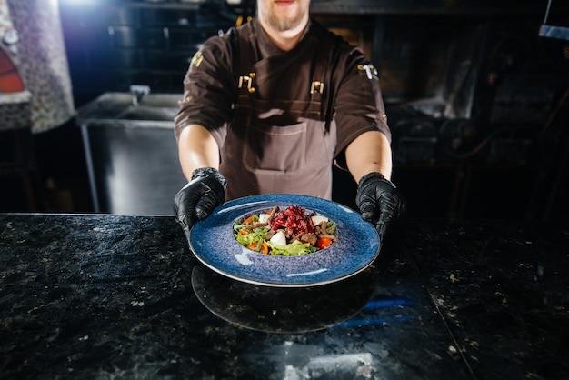 Un chef professionnel sert une salade fraîchement préparée de tomates et de vert de veau avec sauce dans un restaurant gastronomique.