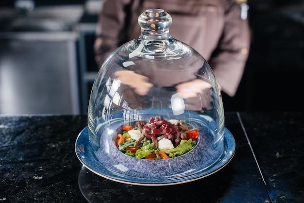 Un chef professionnel sert une salade fraîchement préparée de tomates et de vert de veau avec sauce dans un restaurant raffiné sous un dôme en verre.