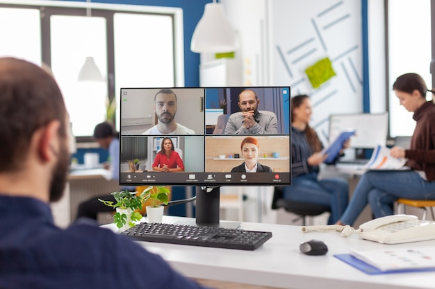 Chef de projet entrepreneur immobilisé en fauteuil roulant parlant par vidéoconférence lors d'une réunion en ligne